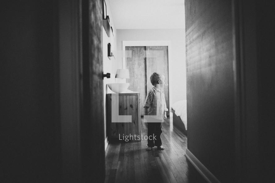 toddler boy standing in a hallway