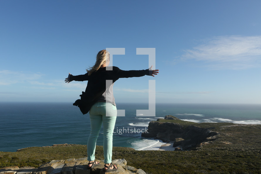 Woman standing on cliff with outstretched arms