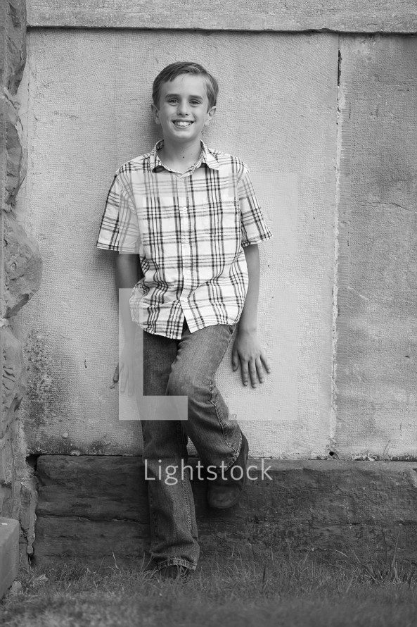 Boy standing in front of concrete wall