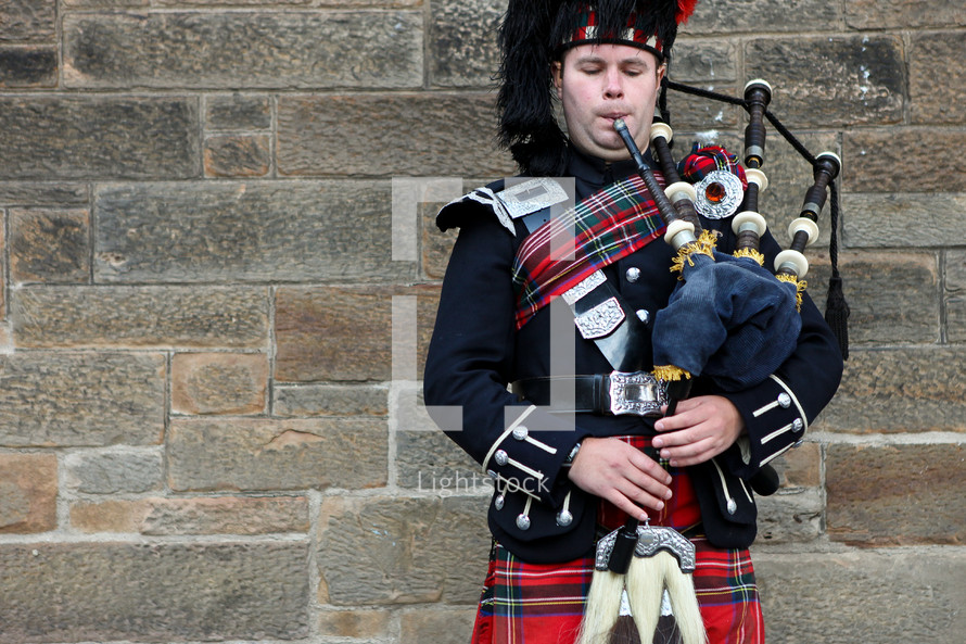A scotland piper playing the bagpipes