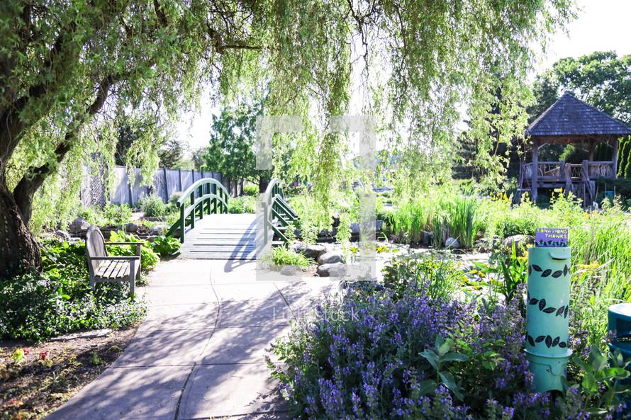 bench under a tree and path through a garden