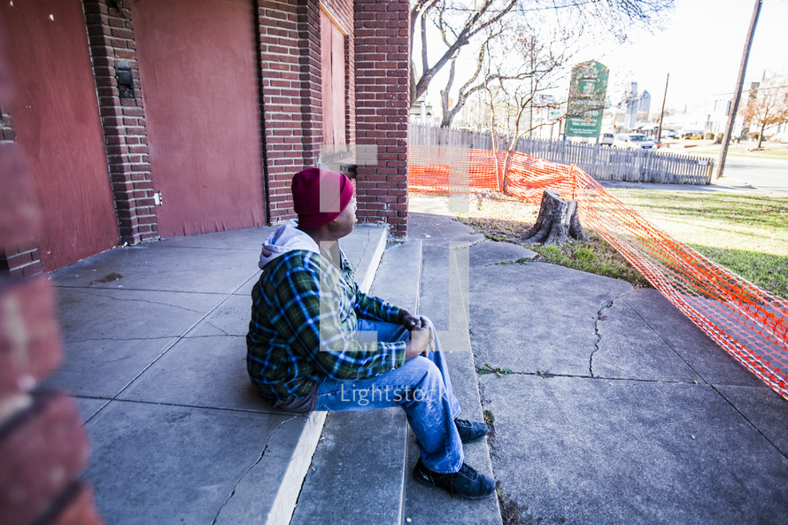 homeless man sitting on stairs in front of a condemned building