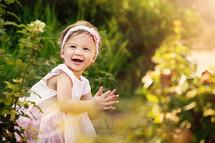 toddler girl outdoors clapping her hands