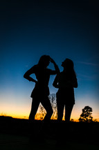 silhouettes of girls standing outdoors at dusk