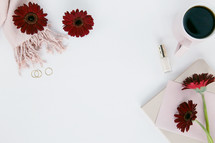 scarf, pink, blush, red gerber daisies, nail polish, coffee mug, stationary, white background, gold rings, pencil