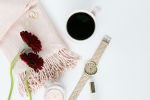 candle, pink scarf, red gerber daisies, watch, nail polish, coffee mug, gold rings, white background