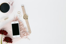 candle, pink scarf, red gerber daisies, watch, nail polish, coffee mug, gold rings, white background, iPhone