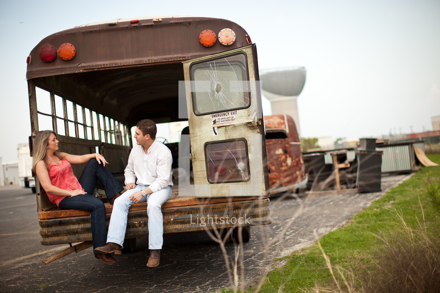 man and woman sitting in the back of an old school bus