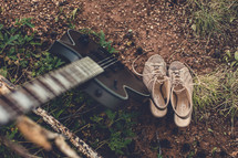 guitar and shoes on the ground