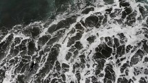 top down drone shot of man paddling out to surf and diving under wave in ocean