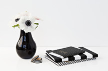 flowers in a black vase and black and white journal