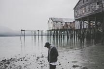 buildings on stilts along a muddy shore in Alaska