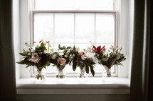 bridal bouquets in vases in a window