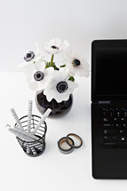 flowers in a black vase, laptop computer, journal, and pens on a desk