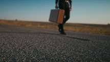 man walking alone on a road carrying a suitcase