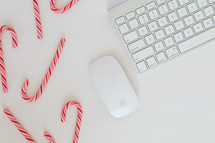 candy canes and computer keyboard with mouse on a desk