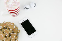 iPhone, gingerbread cookies, bells, and hot cocoa