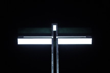 A metal cross against a black background.