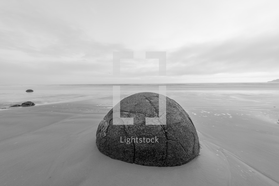 A large round boulder on a sandy beach.