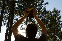 a man holding up a Bible in a pine forest