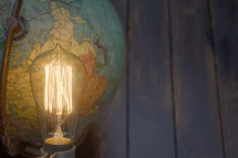 an Edison lightbulb and globe with blue wood boards background