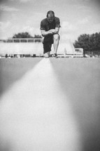man kneeling in prayer on a football field