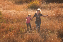 mother and daughter walking in a field