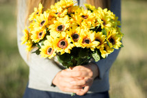 Girl holding bunch of yellow flowers