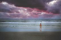 a boy standing on a beach under a stormy sky