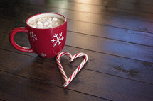 marshmallows and hot cocoa in a red mug and a candy cane