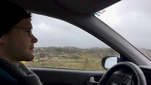man driving through an Iceland countryside