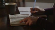 woman reading a Bible and taking notes