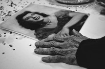 elderly woman looking at an old photograph from her youth