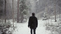 a man walking in a forest in falling snow