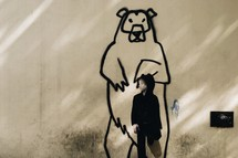 a child in front of a street art painting of a grizzly bear