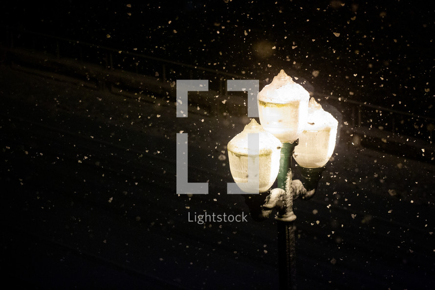 falling snow and a glowing street lamp