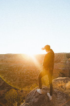 a man standing at the edge of a cliff looking out under bright sunlight