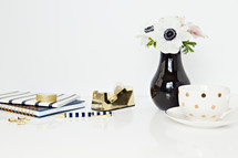 tea cup, tape dispense, gold, clubs, desk, white, flowers, black centers, white background