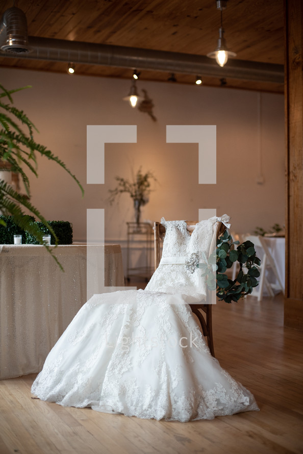 wedding dress in a chair in a reception hall