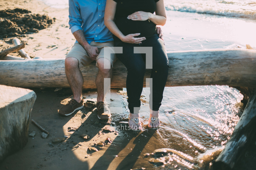 pregnant woman with her hands on her belly and her husbands arms around her