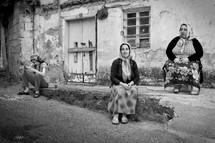 Turkish woman sitting on a street curb in a poor neighborhood in Trabzon Turkey
