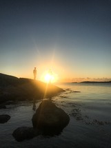 a man stadning on a rocky shore at sunset