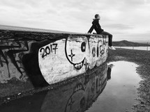 man sitting on a wall covered in graffiti along a shore