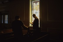a man standing in a church reading a Bible