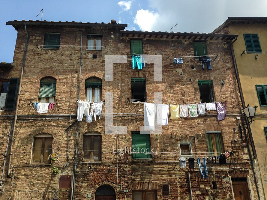clothes hanging from clotheslines on a brick building