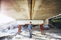 man standing under a pier at a beach