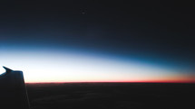 wing of a plane in flight at dawn