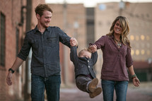 Man and woman in jeans walking in city at dusk swinging toddler boy between them.