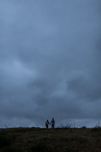Couple standing on a hill holding hands