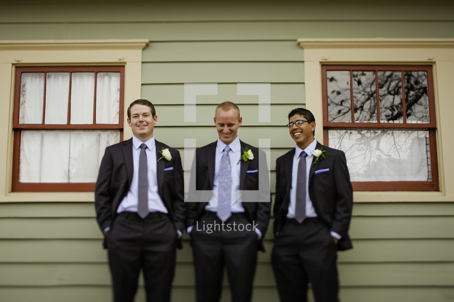 Three groomsmen hangout with hands in their pockets